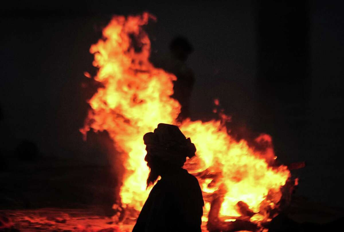 A worker walks in front of a funeral pyre for a person thought to have died from Covid-19 at a mass crematorium site on the banks of the Ganges river on May 05, 2021 in Allahabad, India. India recorded more than 360,000 coronavirus cases in a day for the 12th day in a row on Monday as the total number of those infected according to Health Ministry data neared 20 million. The real figure could be up to ten times higher, many health experts say, due to a lack of widespread testing or reporting, and only patients who succumbed in hospitals being counted. A new wave of the pandemic has totally overwhelmed the country's healthcare services and has caused crematoriums to operate day and night as the number of victims continues to spiral out of control.