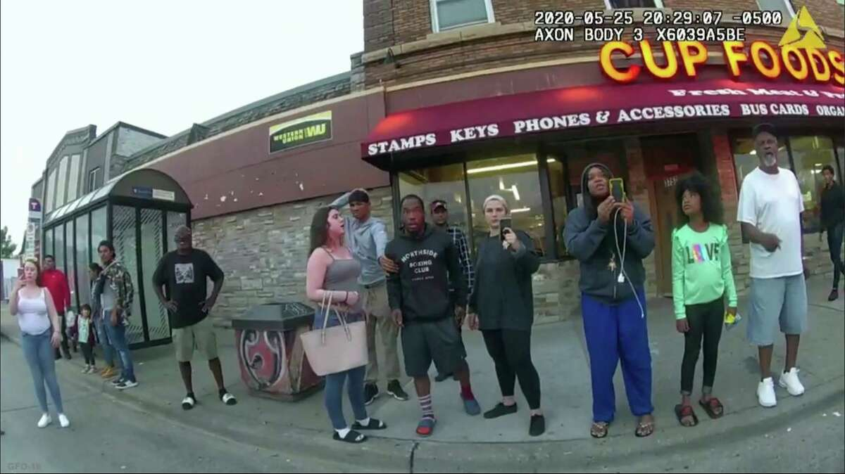 FILE - This May 25, 2020, file image from a police body camera shows bystanders including Alyssa Funari, left filming, Charles McMillan, center left in light colored shorts, Christopher Martin center in gray, Donald Williams, center in black, Genevieve Hansen, fourth from right filming, Darnella Frazier, third from right filming, as former Minneapolis police officer Derek Chauvin was recorded pressing his knee on George Floyd's neck for several minutes in Minneapolis. To the prosecution, the witnesses who watched Floyd's body go still were regular people -- a firefighter, a mixed martial arts fighter, a high school student and her 9-year-old cousin in a T-shirt emblazoned with the word