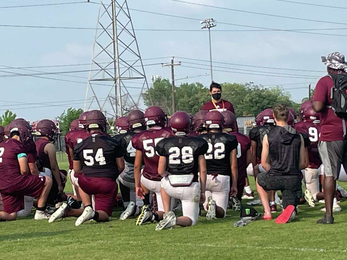 Coach Andres Gomez talks to the Northbrook Raiders after their spring football practice on May 4