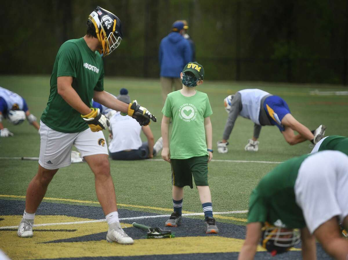 Weston boys lacrosse co-captain Jacob Strouch leads pre-game stretches with honorary team captain, Bode Kloos, 8, of Weston, before the Trojans' game with Brookfield at Weston High School in Weston, Conn. on Monday, May 3, 2021. A group of 2021 Weston athletes, some of which are on the lacrosse team, founded the Weston St. Baldrick's club which has raised over 180 thousand dollars for children's cancer research. Bode is currently enduring his second bout with the disease.