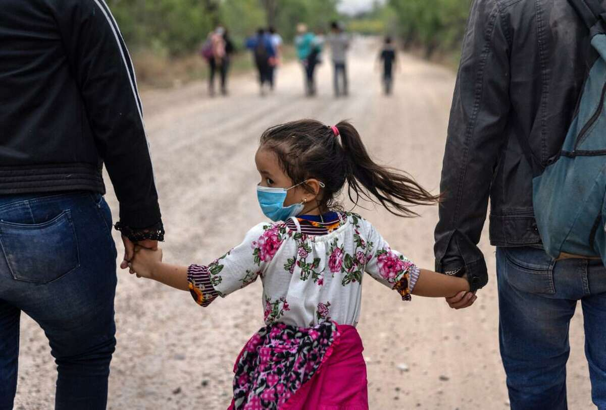 An immigrant child glances back towards Mexico after crossing the border into the United States on April 14, 2021 in La Joya, Texas. Many Central American families who make the arduous journey describe their voyage as harrowing though the length of Mexico. Most pay large sums to smugglers, who often treat them, essentially, as cattle. Others fare even worse. They come nonetheless.