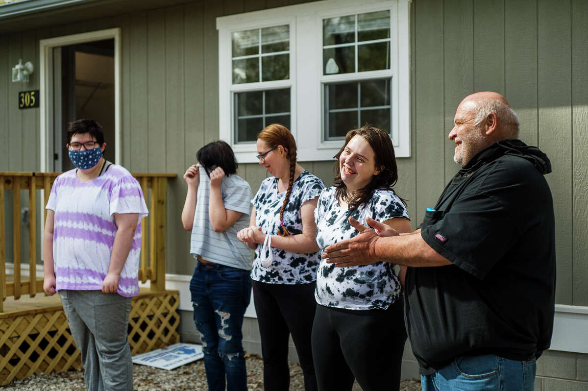 From left, Bethann Billings, 17, Kristiena Billings, 11, Hazel Lutze, Kayte Billings, 13, and Chris Billings smile after Pastor Matt Schramm of Memorial Presbyterian Church provided a blessing for the family's newly built home Wednesday, May 5, 2021 in Sanford. The home was built through a partnership between Habitat for Humanity and the United Way and their collaborative project,