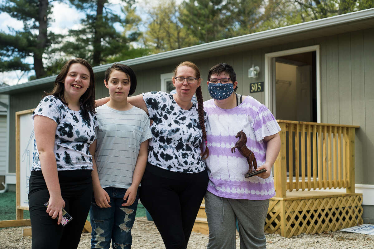 From left, Kayte Billings, 13, Kristiena Billings, 11, Hazel Lutze and Bethann Billings, 17, pose for a photo in front of their newly built home Wednesday, May 5, 2021 in Sanford. The home was built through a partnership between Habitat for Humanity and the United Way. (Katy Kildee/kkildee@mdn.net)
