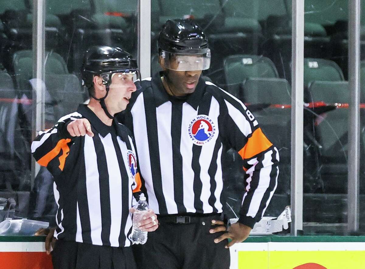 AHL official Jordan Samuels-Thomas speaks with another official during a hockey game between the Texas Stars and Iowa Wild at the H-E-B Center on Feb. 26, 2021 in Cedar Park, Texas. Samuels is a former Quinnipiac University standout.
