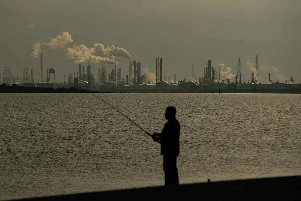 People fish along the Texas City Dike across from the Texas City industrial complex, including the Marathon refinery.