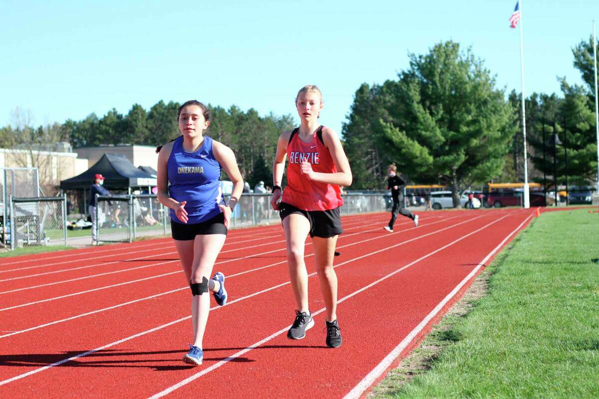 Blanca Andres races alongside Benzie Central's Caitlyn Pallin in the 1600 meters on May 5. (Robert Myers/Record Patriot)