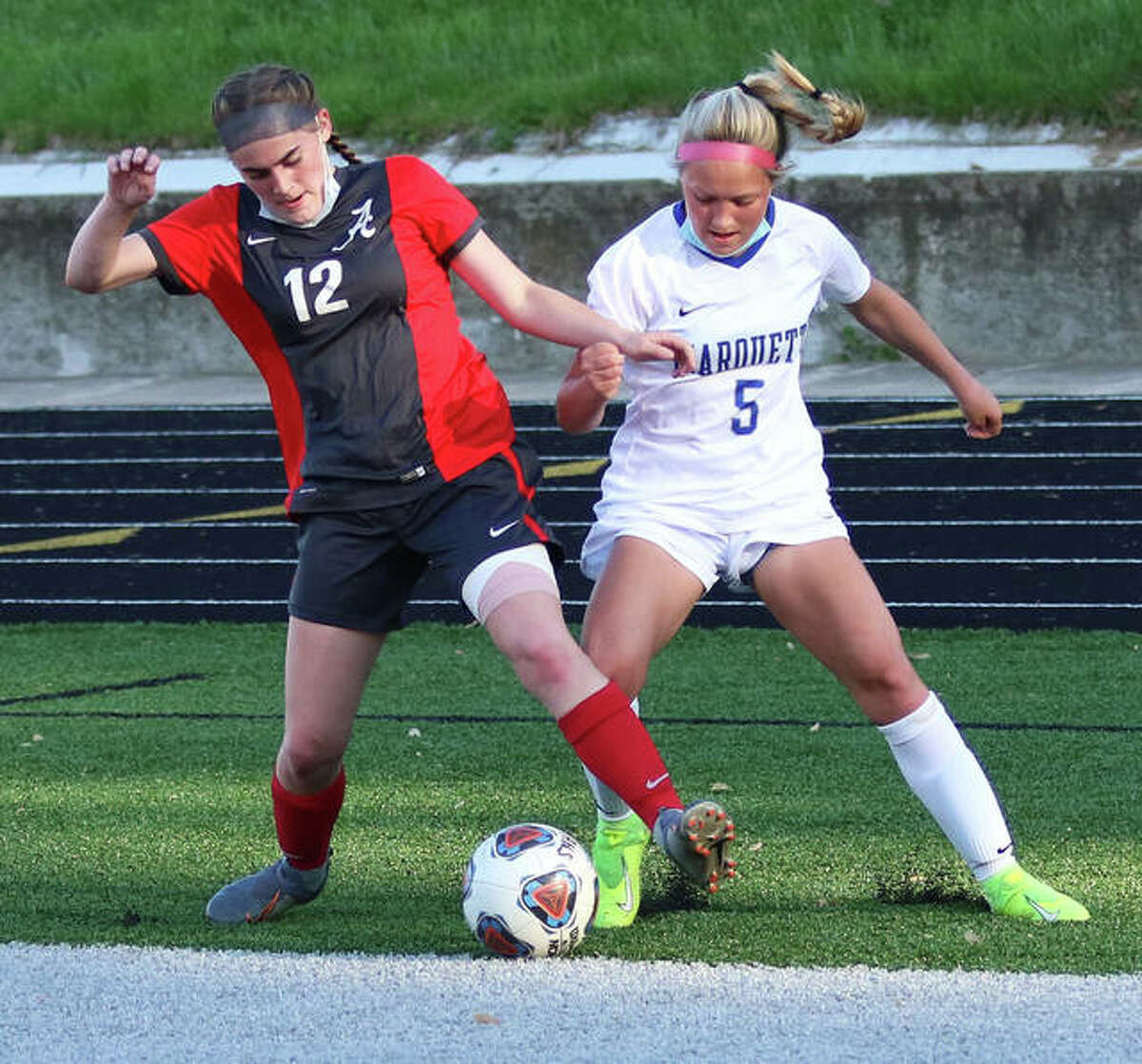 Marquette's Clare Antrainer (5) and Alton's Ainsley Redman battle for possession of the ball deep in Alton's end in the first half Wednesday at Public School Stadium in Alton.