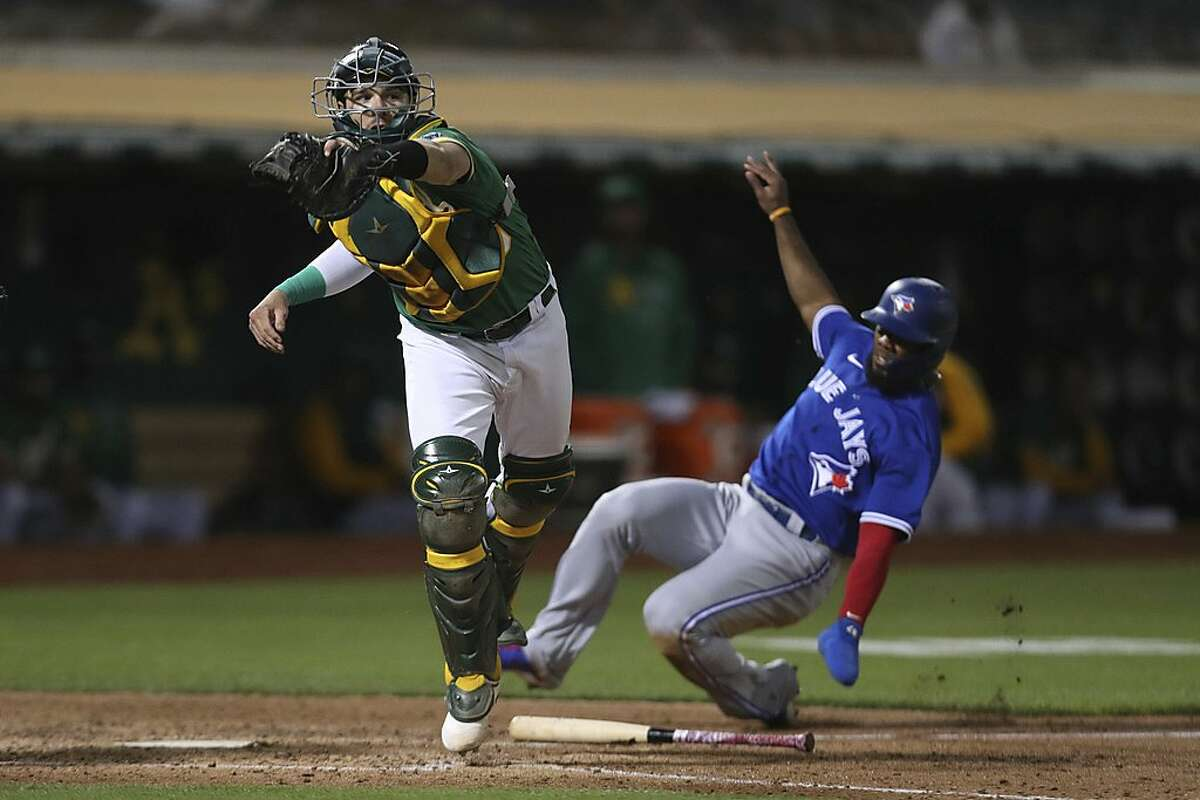 Toronto Blue Jays' Teoscar Hernandez slides into home as Oakland Athletics' Austin Allen fields the throw on a sacrifice bunt by Cavan Biggio during the eighth inning of a baseball game in Oakland, Calif., Wednesday, May 5, 2021. (AP Photo/Jed Jacobsohn)