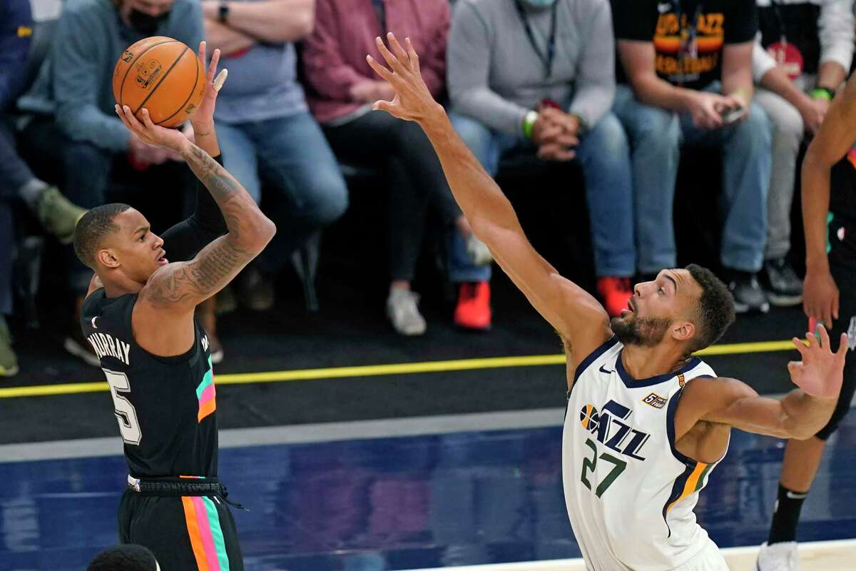 Spurs guard Dejounte Murray (5) shoots as Utah Jazz center Rudy Gobert (27) defends during the first half of an NBA basketball game Wednesday, May 5, 2021, in Salt Lake City.