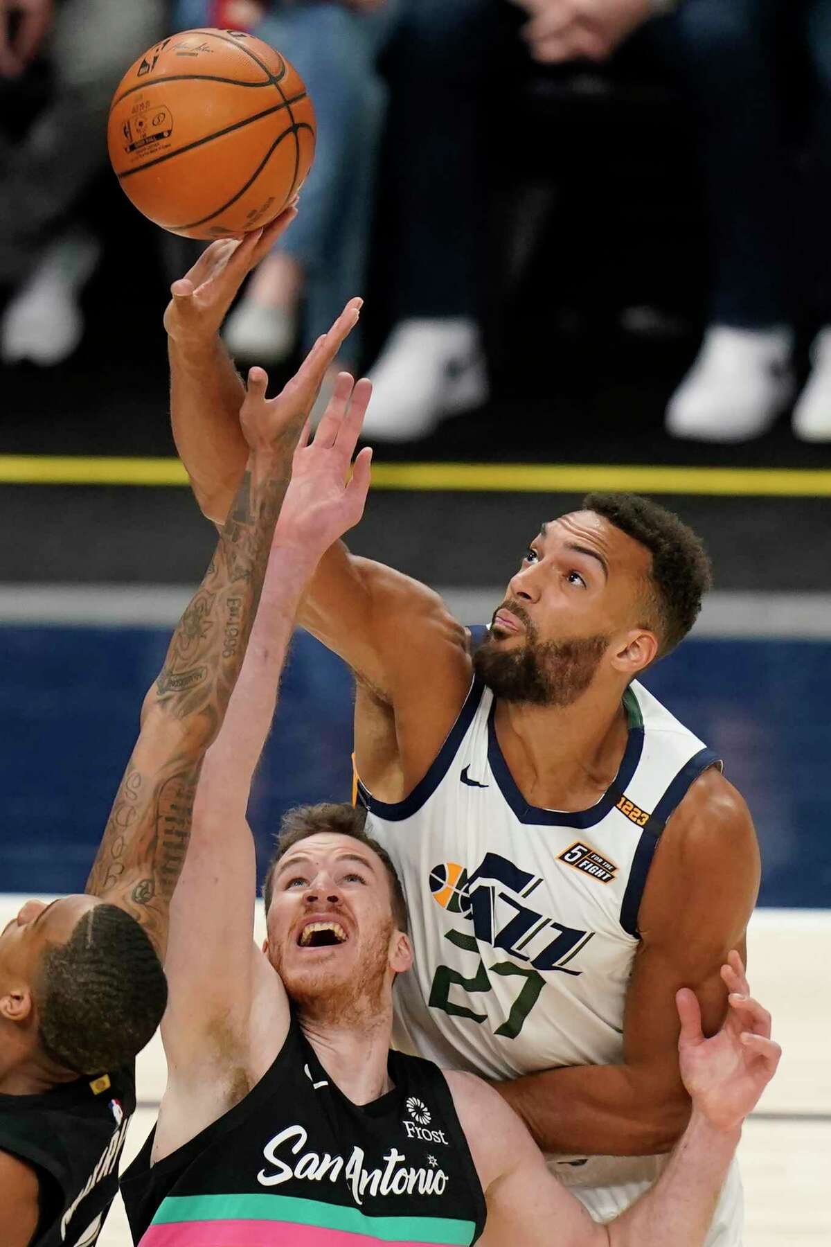 The Spurs' Jakob Poeltl, middle, and Utah Jazz center Rudy Gobert (27) reach for a rebound during the first half of an NBA basketball game Wednesday, May 5, 2021, in Salt Lake City.