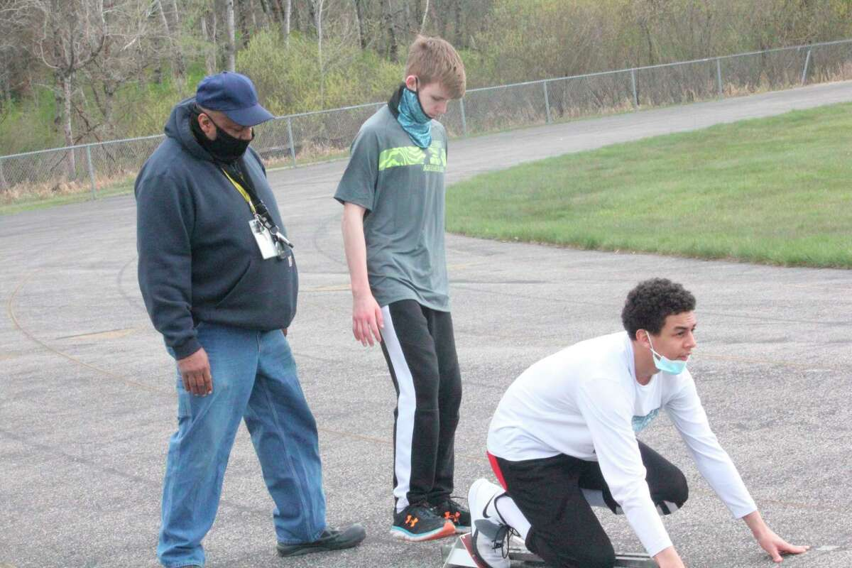 Baldwin boys track coach Bob Watkins (left) works with JacobCutler (center) and Anthony Austinon the track during a practice last week. (Star photo/John Raffel)