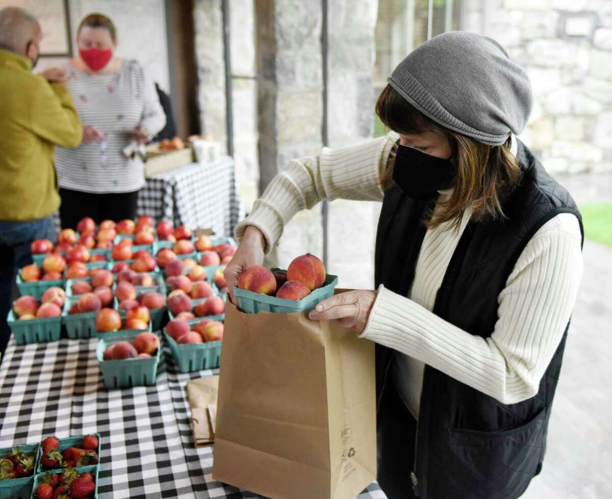 Gianna Bavido helps a customer at the Double L Market stand at the Garden Markets in the Tavern Garden at the Greenwich Historical Society in the Cos Cob section of Greenwich, Conn. Wednesday, May 5, 2021. The market will be held on alternating Wednesdays rain or shine featuring all things