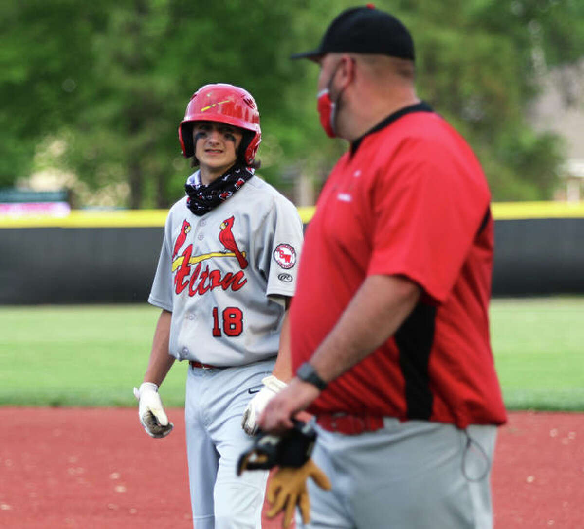 Alton's James Vambaketes (left) looks to first base coach Brett Huff during Monday's SWC loss in O'Fallon. Vambaketes had two hits and picked up a save in Wednesday's rematch with the Panthers in Godfrey.