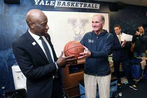In 2019, Yale University men's basketball head coach James Jones (left) is presented with the game ball by David Swensen, Chief Investment Officer for the Yale University Endowment, in the locker room after his 300th career win over Brown at Lee Amphitheater in New Haven.