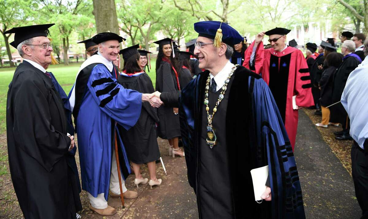 Yale University Chief Investment Officer David Swensen, left, shakes hands with Yale University President Peter Salovey, center, during Yale University's 318th Commencement in 2019 in New Haven.