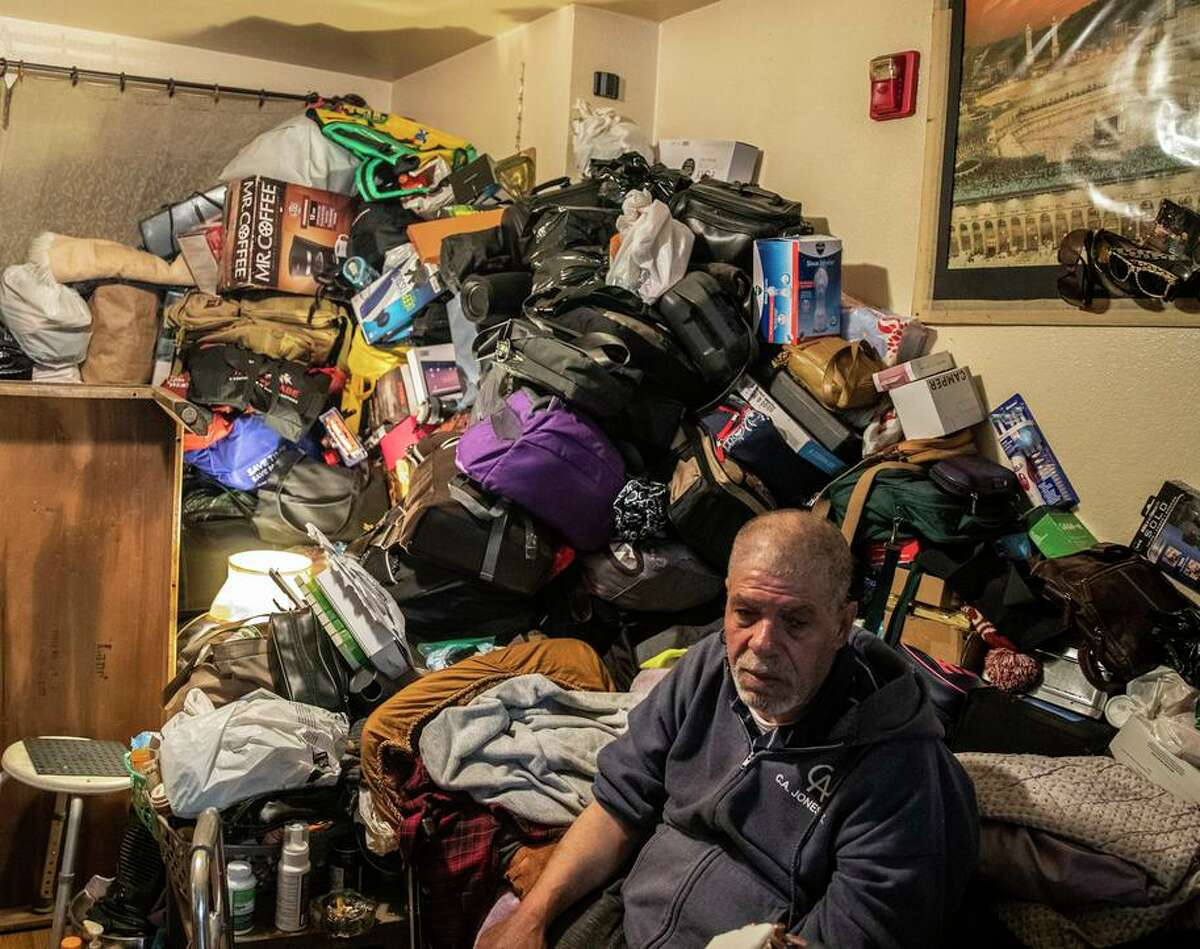 Ahmad Alaydi sits in front of a pile of belongings, stashed after a broken fire sprinkler flooded his home at Plaza East Apartments.