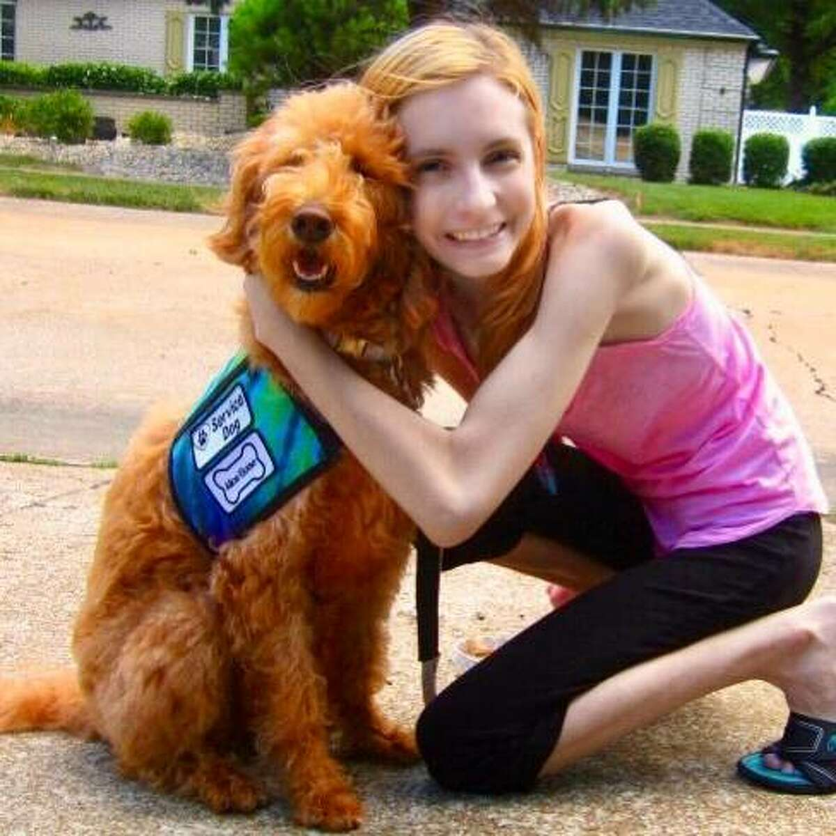 Edwardsville resident Sarah Kathryn Frey with her service dog, Alice Eloise. Frey, who has dealt with severe illness and disability for most of her life, hopes to inspire others with her new book,