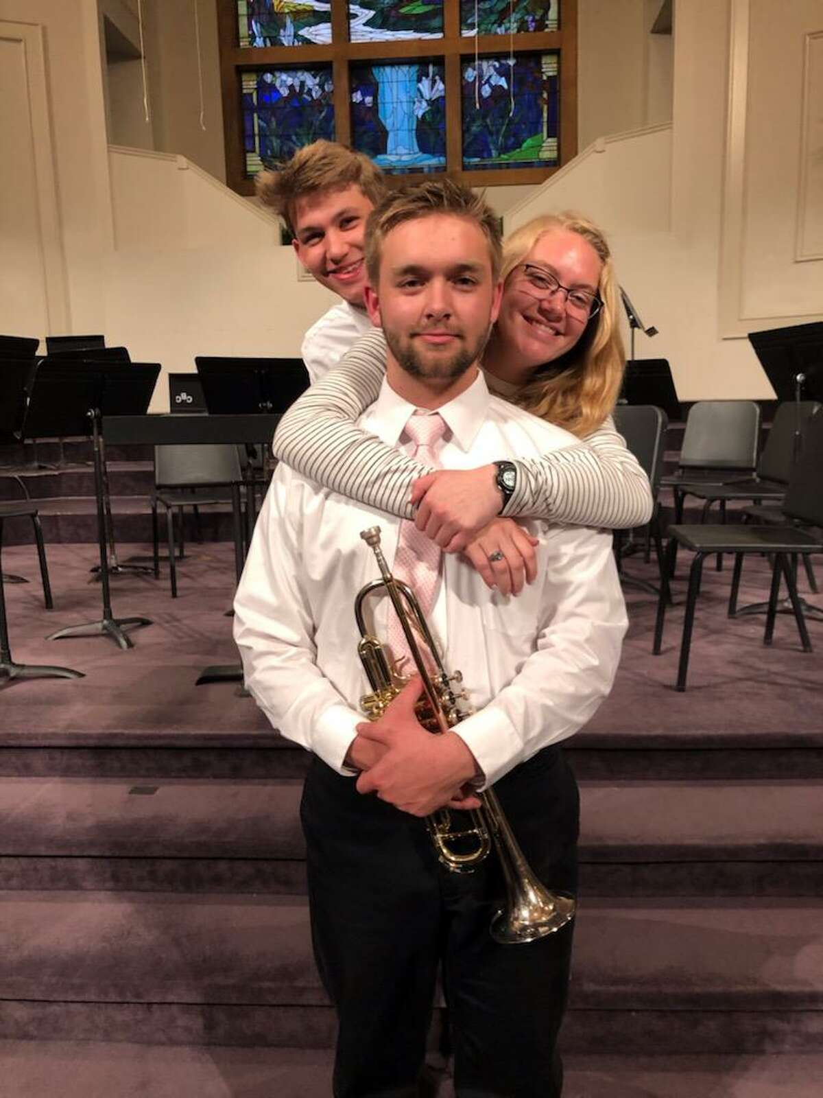 Calvary Baptist Academy senior trumpeter Caleb Wallace is pictured with his younger brother, Isaac Wallace, left, and his older sister, Savannah Wallace.