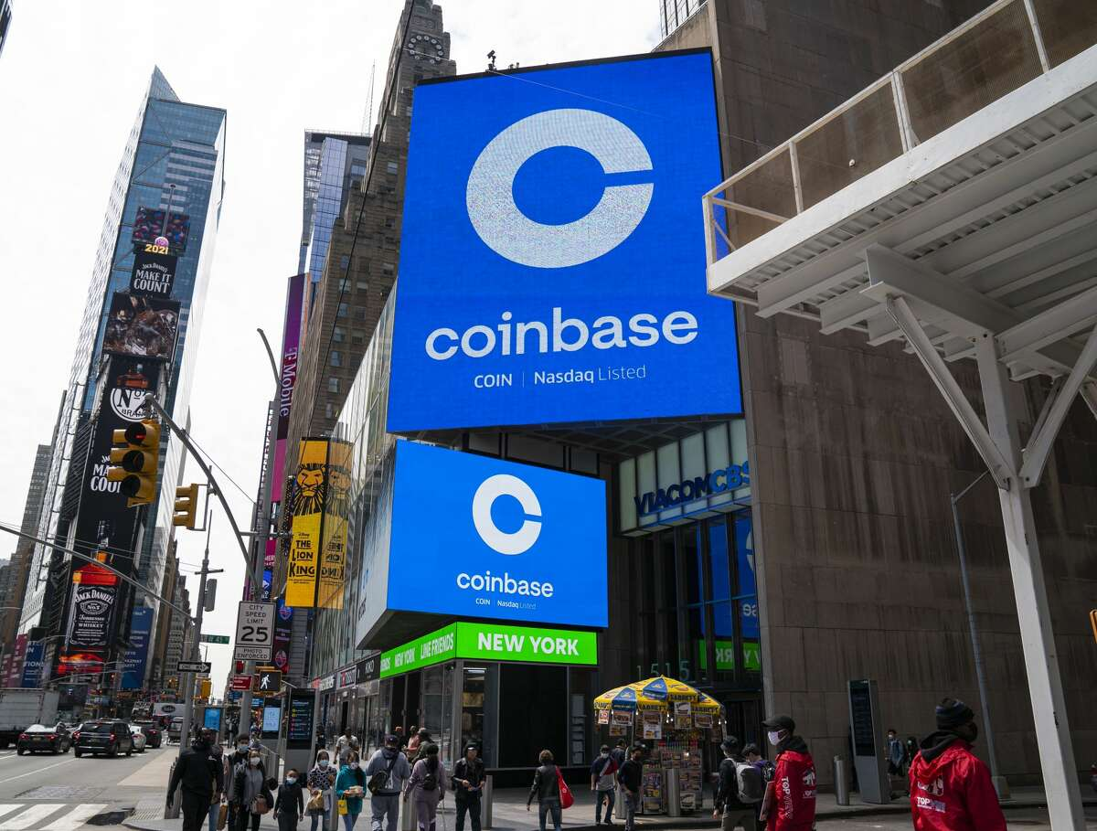 Monitors display Coinbase signage during the company's initial public offering at the Nasdaq market site April 14, 2021, in New York City.