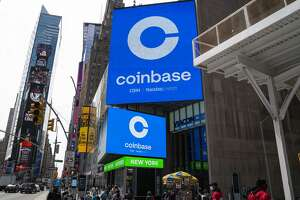 Monitors display Coinbase signage during the company's initial public offering (IPO) at the Nasdaq market site April 14, 2021 in New York City.