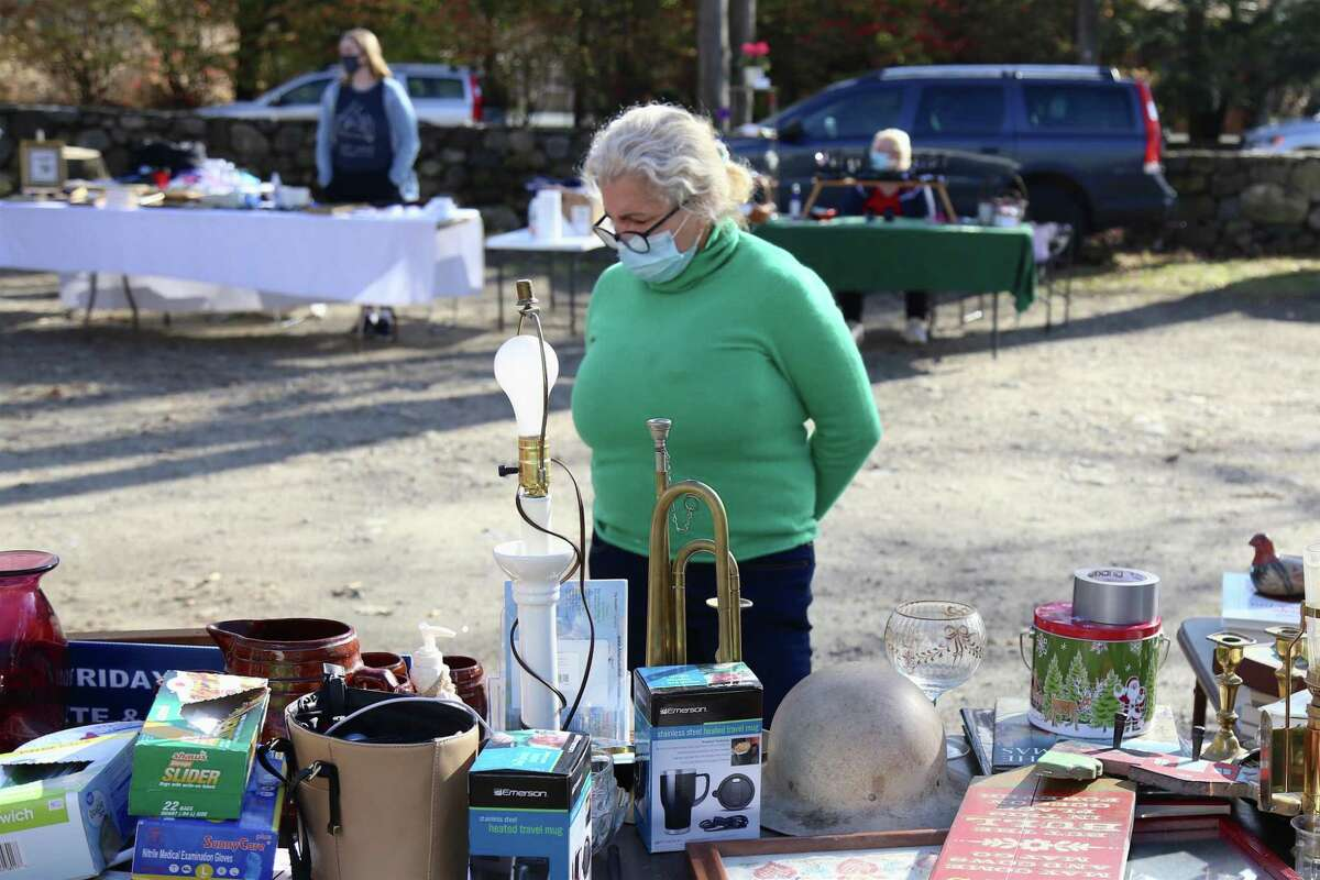 Zelda Monteiro of Fairfield looks over the stuff at the Norfield Grange's Black Friday Trunk Sale on Nov. 27, 2020, in Weston, Conn.