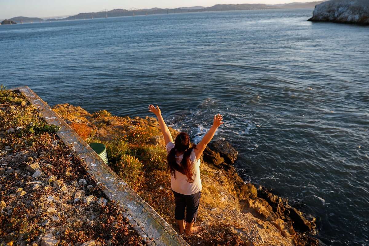 Innkeeper Desiree Heveroh momentarily raises her arms as she watches the sunset from the East Brother Light Station on May 3.
