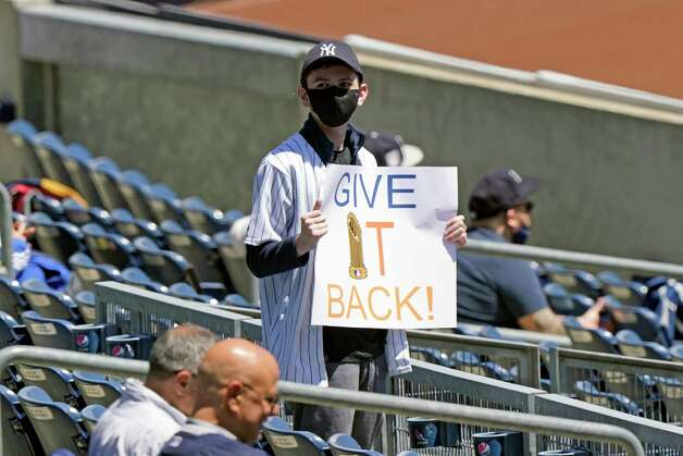 A fan holds a sign referring to the Astros 2019 World Series win before the start of a baseball game between the New York Yankees and the Houston Astros, Thursday, May 6, 2021, at Yankee Stadium in New York. (AP Photo/Kathy Willens) Photo: Kathy Willens, Associated Press / Copyright 2021 The Associated Press. All rights reserved.