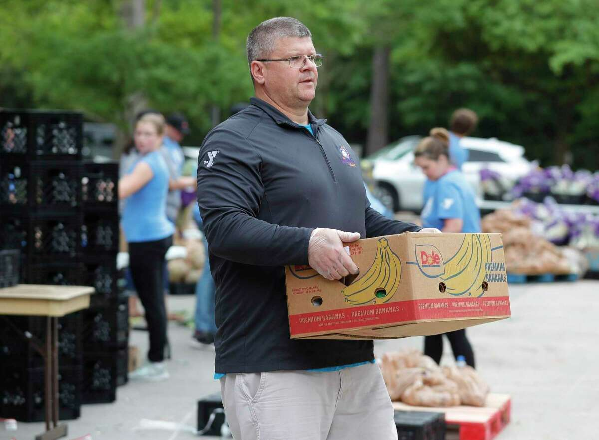 Scott Harper carries fruit to a car as volunteers and staffs with The Woodlands Family YMCA and the Montgomery County Food Bank help give out food to families, Saturday, March 28, 2020, in The Woodlands. Two hundred families received 40-pounds of food in the organizations' mobile market.