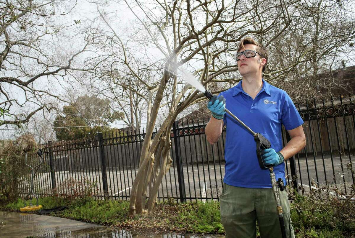 """Scott Wessels power-washes his friend's driveway and house Friday, Feb. 26, 2021, in Houston. Wessels was laid off from an oil and gas job, and he started a power-washing company to make money. """"It was overwhelming,"""" he said of the experience of starting a business. """"This is the bridge from what I used to do, to whatever I'm doing next,"""" he said."""