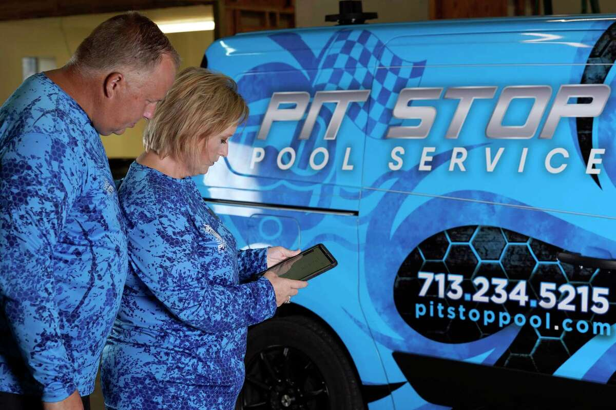 Amy and Cody Morgan look over their next appointment, Friday, Sept. 4, 2020, in Cypress, Texas. The couple, who lost their jobs as corporate executives during the coronavirus pandemic, decided to start a pool servicing company, Pit Stop Pools. (AP Photo/David J. Phillip)