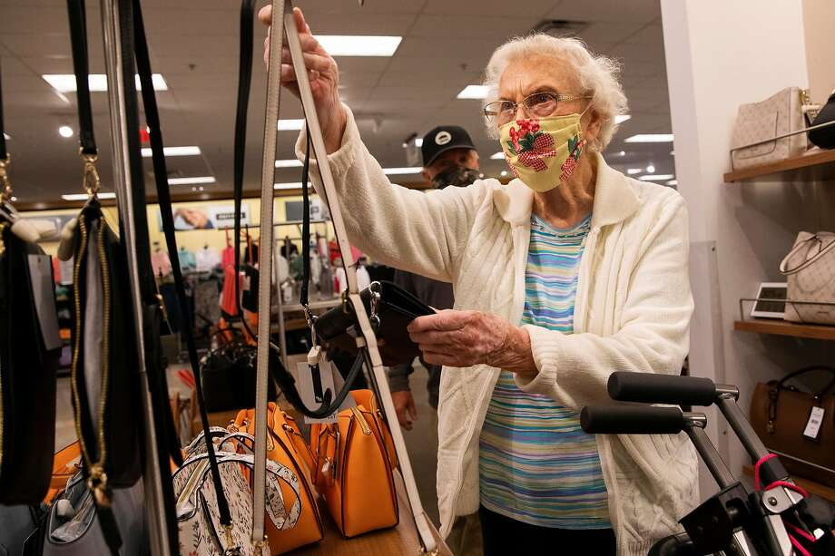 David Mann, 63, watches nearby as Marjorie Mann, 94, picks out a small purse at Kohl's in Alameda. Photo: Jessica Christian / The Chronicle