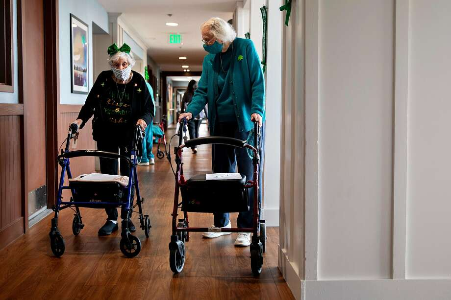 Marjorie Mann, 94, joins Helen Caroll, her fellow resident and former third-grade teacher to her children, on a St. Patrick's Day scavenger hunt at Waters Edge Lodge in Alameda in March. Photo: Jessica Christian / The Chronicle