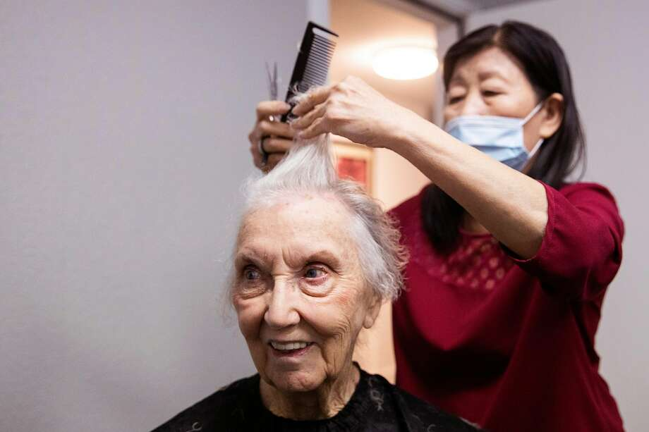 A hairstylist gives Marjorie Mann, 94, a haircut and perm at Waters Edge Lodge in Alameda in March. Photo: Jessica Christian / The Chronicle