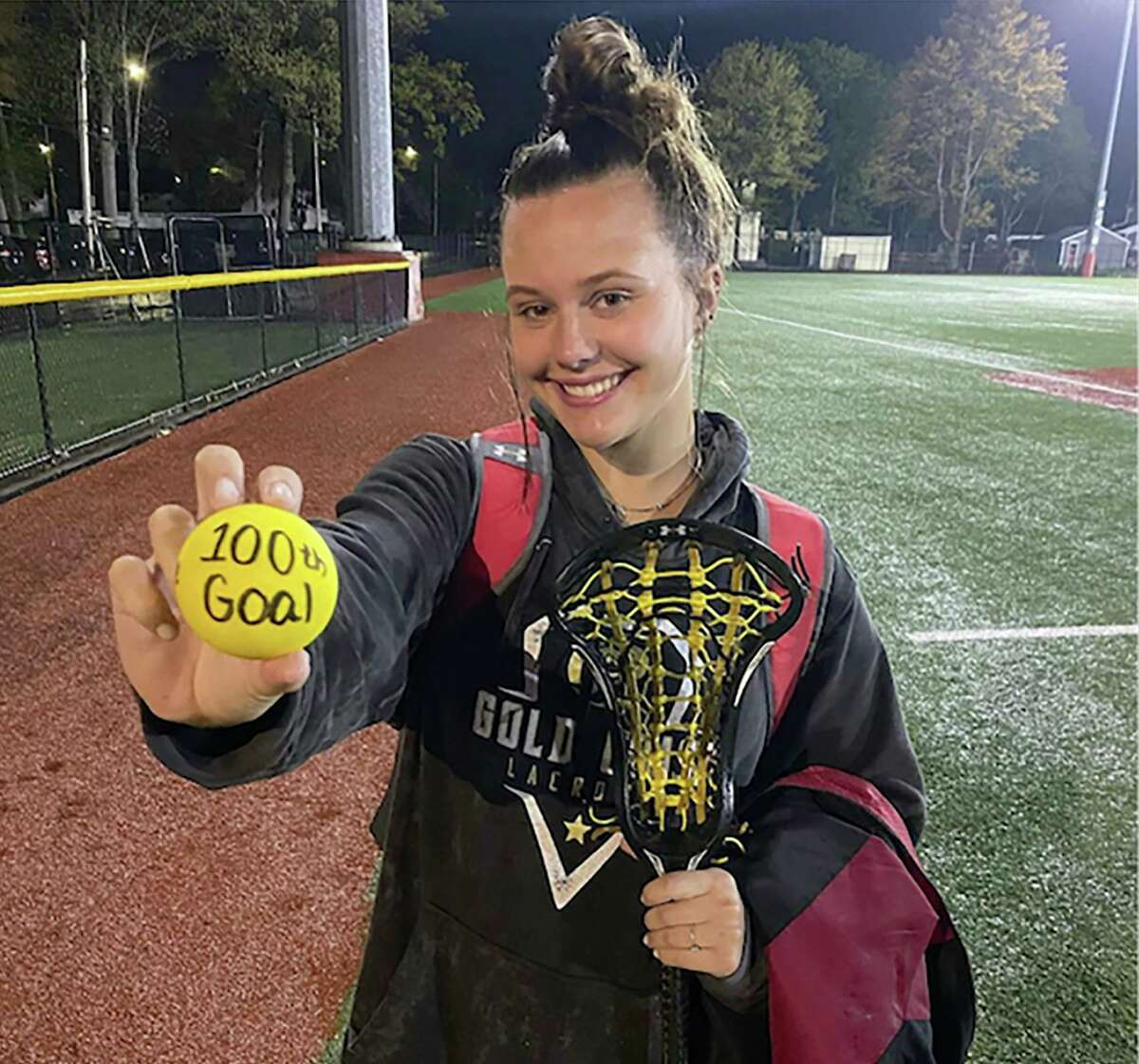 Stratford's Edie Threshie displays a lacrosse ball marking her 100th career goal after a game against Brookfield on Saturday.