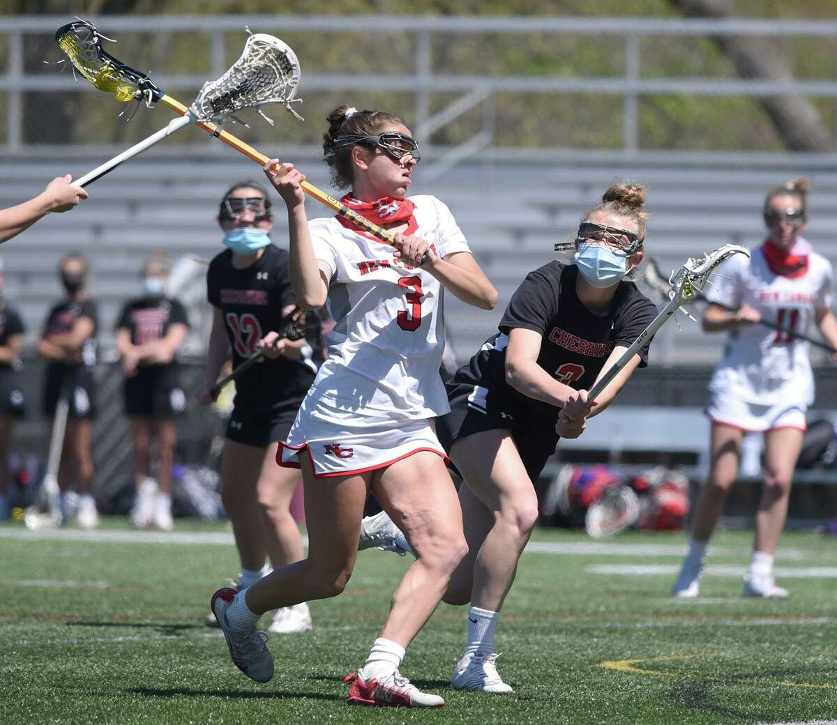 New Canaan's Dillyn Patten (3) lines up for a shot while Cheshire's Hannah Merritt (3) defends during a girls lacrosse game at Dunning Field on Saturday.