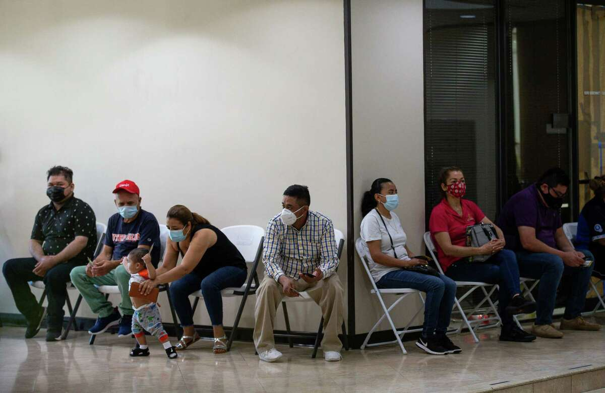 People wait to get Moderna's COVID-19 vaccine at the Consulado General de El Salvador in southwest Houston on Thursday.