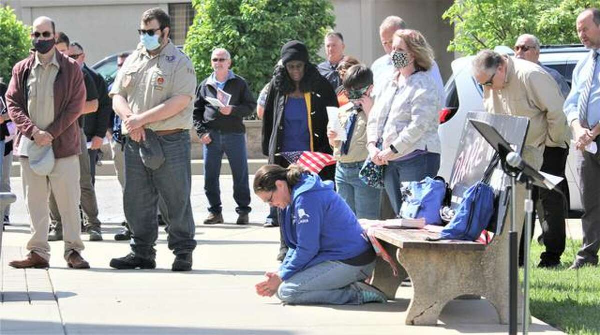 Emily Grace kneels to pray during National Day of Prayer observance at the Granite City Hall Thursday. The nationwide annual observance, which had been heavily curtailed last year because of COVID, was back this year with a variety of in-person and remote events. Local events include two live meetings in Granite City, another in Jerseyville, and a remote event in Alton.