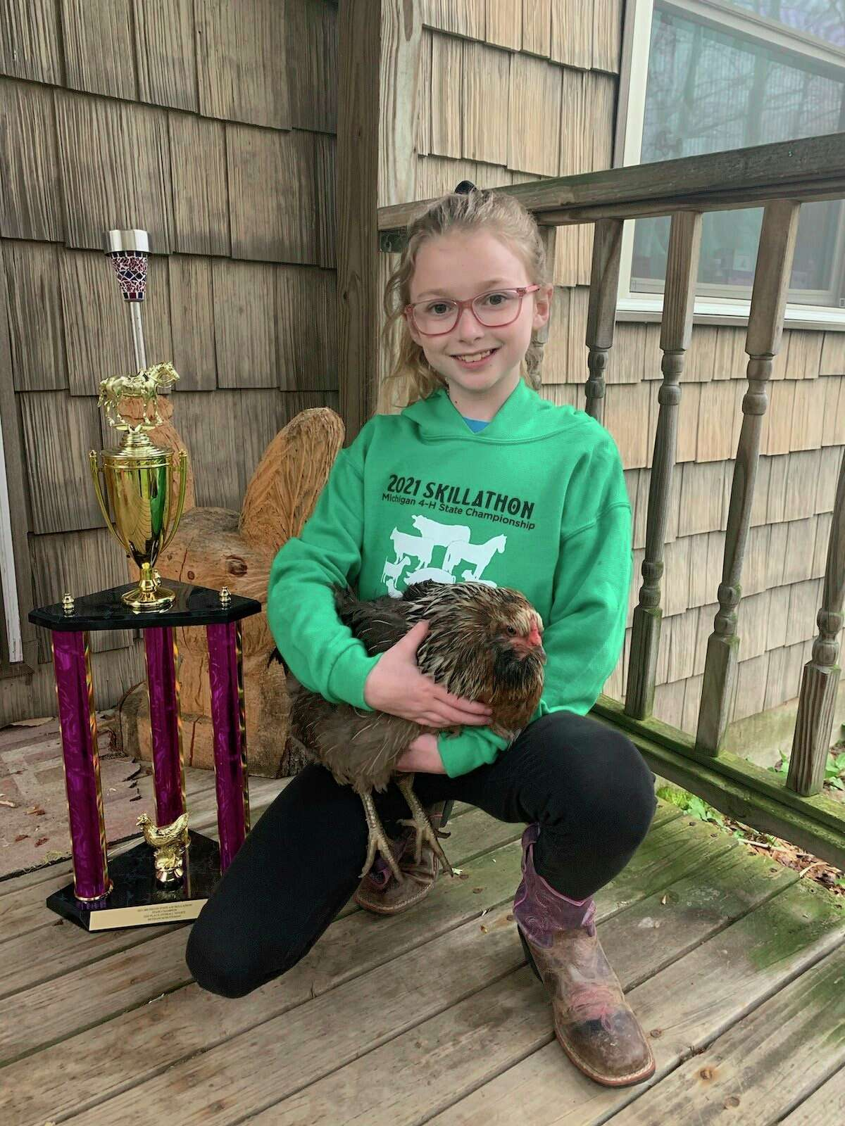 BethaniSchuiteman, age 10 of the Manistee County 4-H, posesnext to her sponsored trophy from the 2021 Michigan 4-H Skillathon.(Courtesy Photo/Jamie Smith)