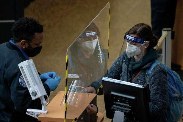 A traveler passes through security screening at Seattle-Tacoma International Airport on November 29, 2020 in SeaTac, Washington.
