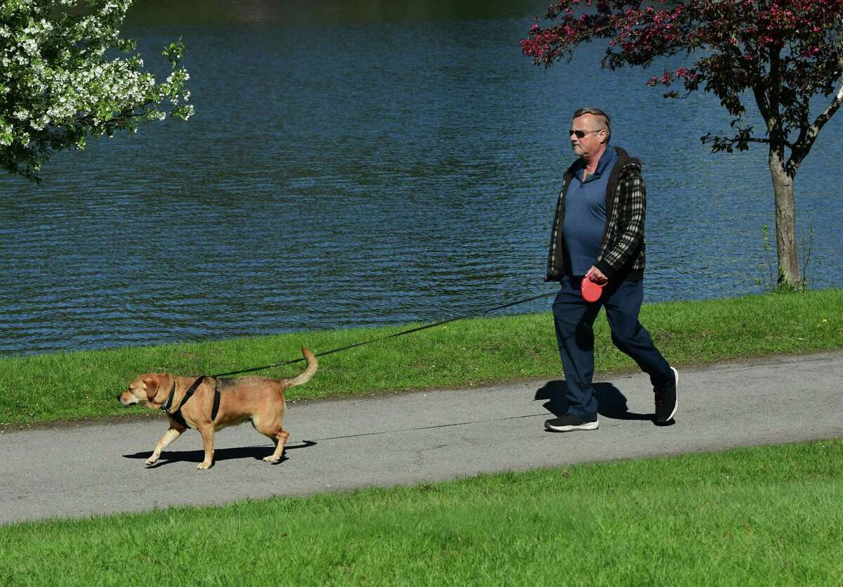 A man is seen walking. dog around Iroquois Lake in Central Park on Thursday, May 6, 2021 in Schenectady, N.Y. (Lori Van Buren/Times Union)