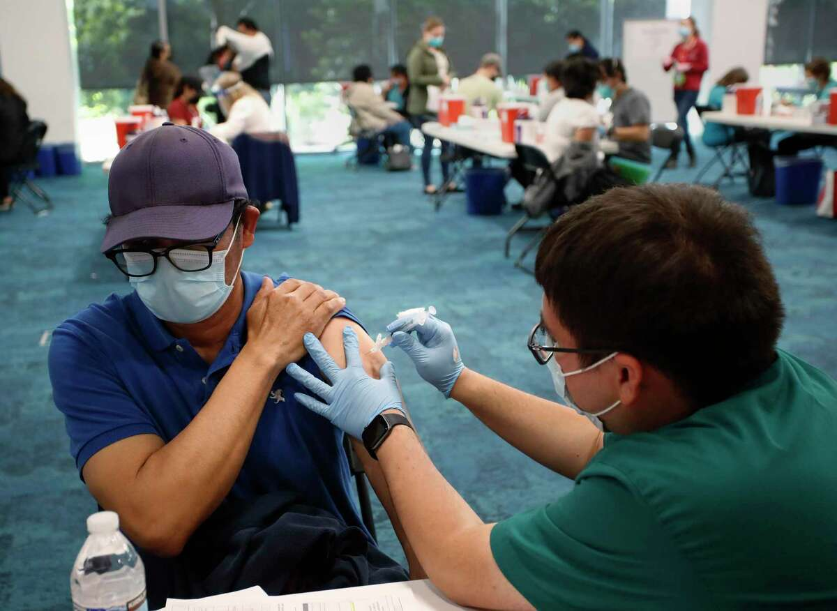 Mariano Zelaya of Redwood City receives his COVIDA-19 vaccination from Carlos Martinez at Facebook headquarters in Menlo Park in April.