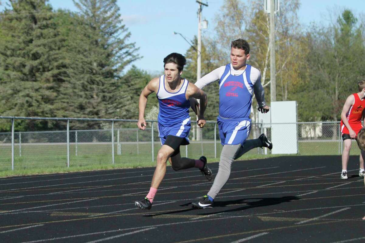Manistee Catholic Central's Mateo Barnett takes the handoff from teammate Justin Stickney in the 400-meter relay on Wednesday during a West Michigan D League jamboree in Brethren. (Dylan Savela/News Advocate)