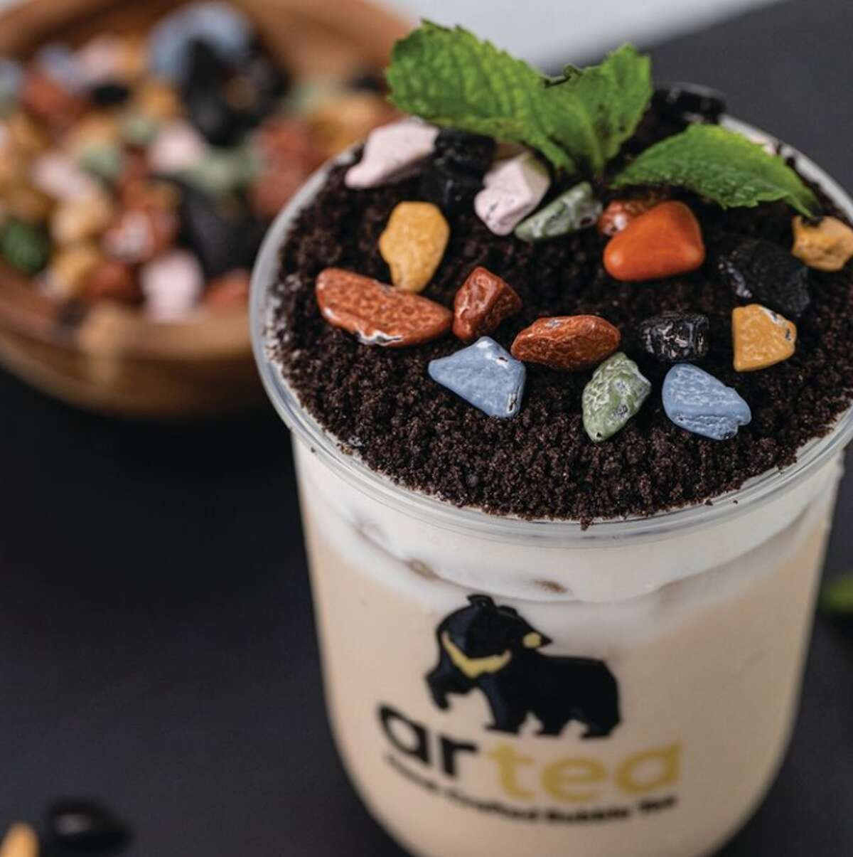 """One of Artea's signature specialty drinks is a """"Bonsai Milk Tea."""" As its name suggests, the drink comes in a cup with a topper which serves as a landscape for a potted plant. In this case, the vegetation is fresh mint."""