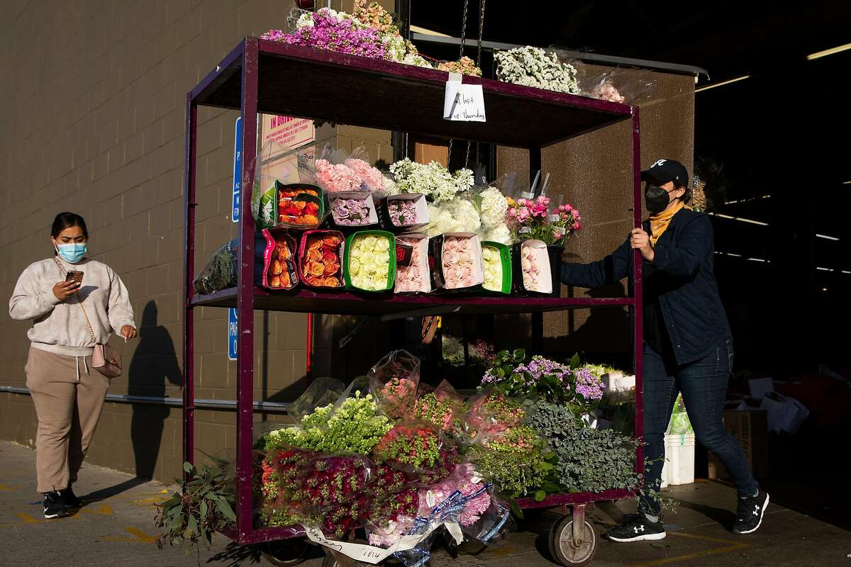Courtney Sayner moves a cart0 of flowers after shopping at the San Francisco Flower Market.