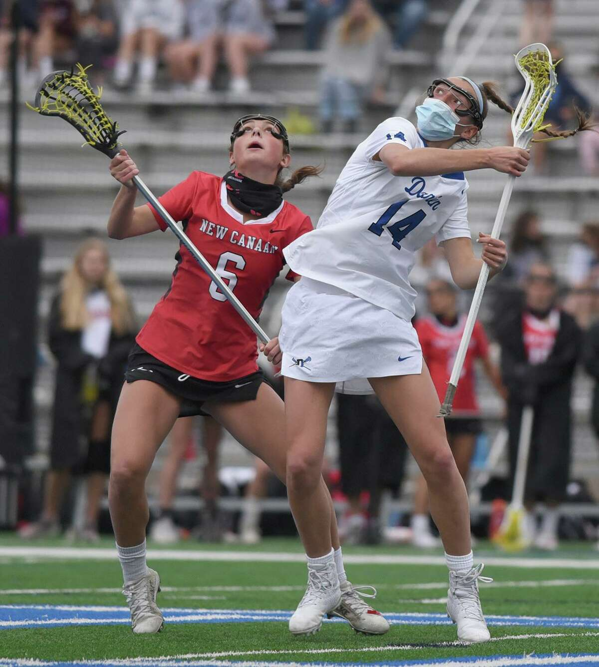New Canaan's Kaleigh Harden (6) and Darien's Colette Quinn (14) battle on a draw during a game on Monday.