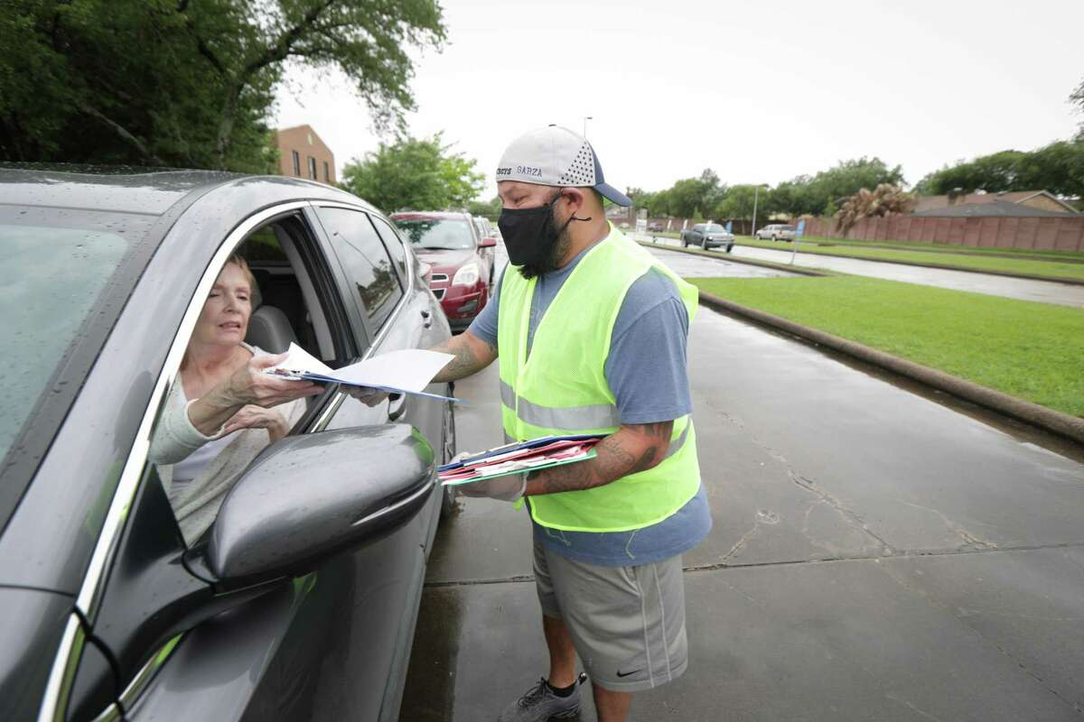 Volunteer Eddie Garza hand consent forms to people in line before a COVID-19 vaccine clinic for the community at CrossRoads United Methodist Church Friday, April 30, 2021, in Houston.