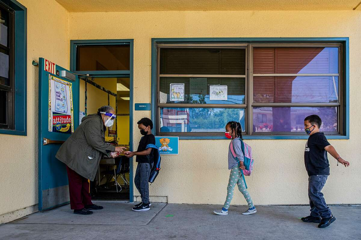 Eulalia Thomas gives Cameron Brown, 7, and other first-graders hand sanitizer as they enter class at Cleveland Elementary School in Oakland.