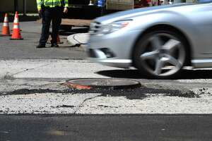 A car dodges a raised manhole cover as paving begins on Summer Street in Stamford, Conn. Thursday, May 6, 2021. Many residents have suffered flat tires from the raised manhole covers on the road, comparing it to an obstacle course.