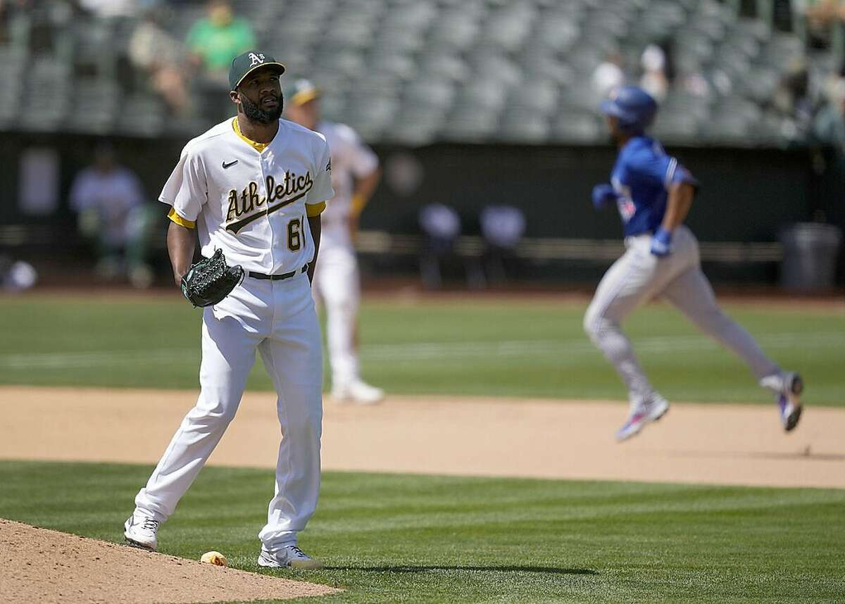 Oakland Athletics relief pitcher Reymin Guduan (61) stands on the edge of the mound as Toronto Blue Jays' Marcus Semien, right, runs the bases after hitting a solo home run during the seventh inning of a baseball game in Oakland, Calif., Wednesday, May 6, 2021. (AP Photo/Tony Avelar)