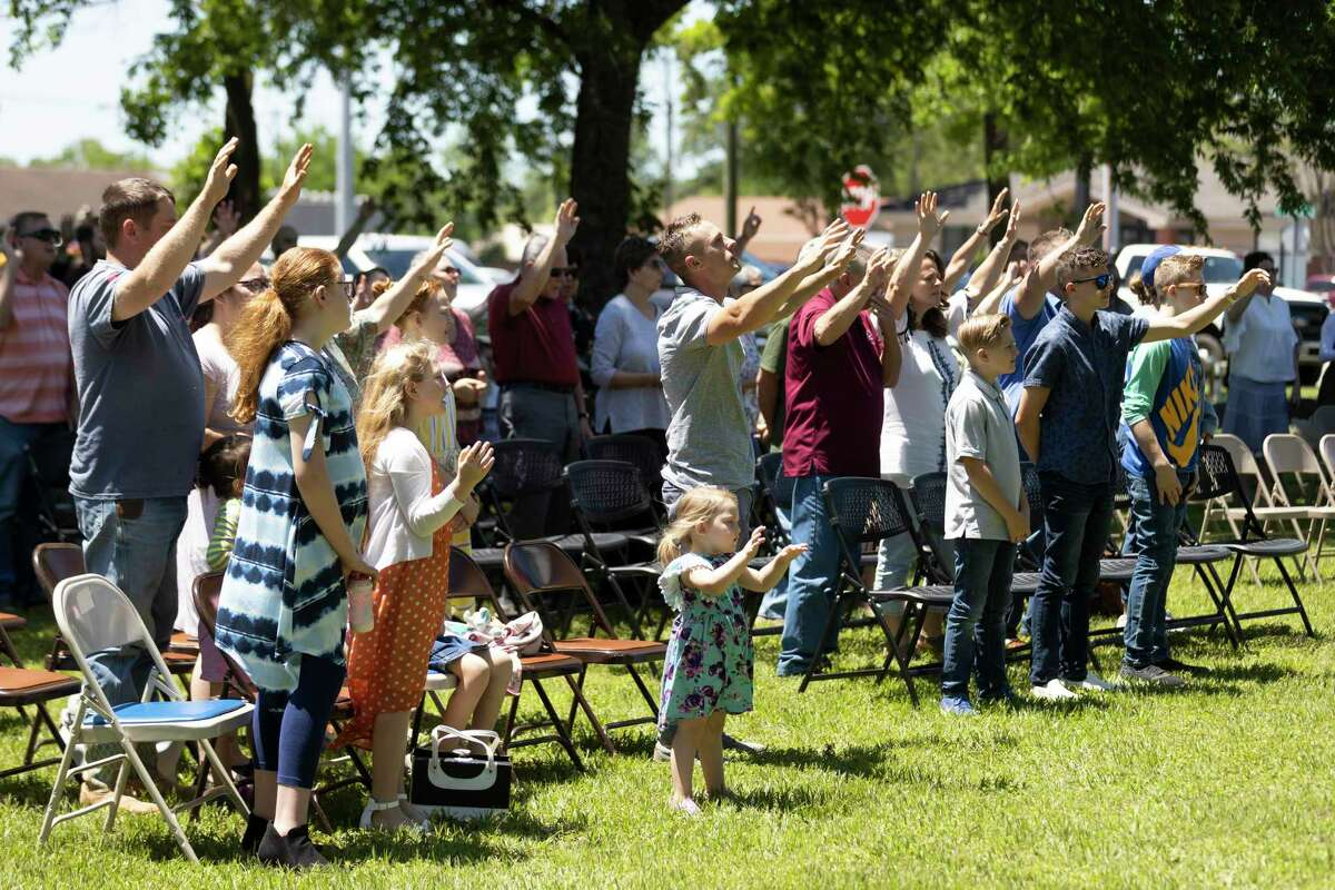 Dozens of attendees participate in a prayer during a National Day of Prayer celebration behind Montgomery County Justice of Peace Precinct 1, Thursday, May 6, 2021, in Willis. Local faith leaders and politicians spoke at this year's event.